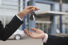 Salesman handing over car keys, close up on hands Royalty Free Stock Photo