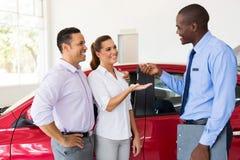 Salesman handing over new car Stock Photo