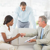 Salesman handing pen to client to sign the contract Royalty Free Stock Photos