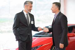 Salesman handing sports car keys to customer. Salesman royalty free stock images