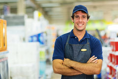 Salesman hardware store. Happy young salesman standing in hardware store Royalty Free Stock Photos