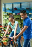 Salesman helping customer. Smiling handsome salesman helping female customer to choose the best bike stock photo