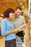 Salesman helping woman finding groceries Stock Images