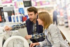 Salesman helping woman to choose washing machine Royalty Free Stock Image