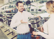 Salesman helps to choose the saucepans Royalty Free Stock Photo