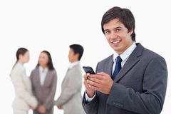 Salesman holding cellphone with team behind him Stock Photography