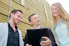 Salesman holding clipboard with couple. Salesman royalty free stock images