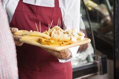 Salesman Holding Cutting Board With Assorted Cheese Royalty Free Stock Photos