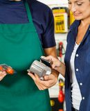 Salesman Holding Electronic Reader While Customer Stock Photos