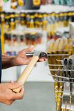 Salesman Holding Hammer In Hardware Store. Cropped image of senior salesman holding hammer in hardware store stock photography