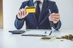 Salesman holding a key, credit card and calculating a price of s stock image