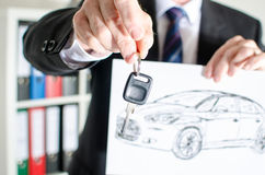 Salesman holding a key and showing a car design Royalty Free Stock Photography