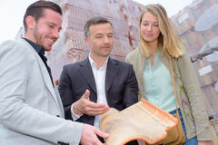 Salesman holding modern rooftile for couple to see Royalty Free Stock Photos