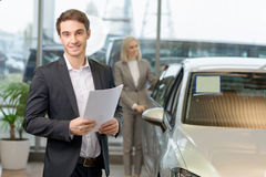 Salesman is holding papers for his client Royalty Free Stock Photos