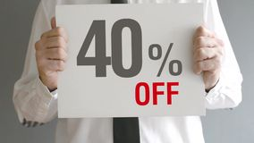 Salesman holding sale tag with forty percent sales discount price. Consumerism concept. stock footage