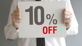 Salesman holding sale tag with ten percent sales discount price. Consumerism concept. stock footage