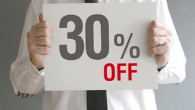 Salesman holding sale tag with thirty percent sales discount price. Consumerism concept. stock video