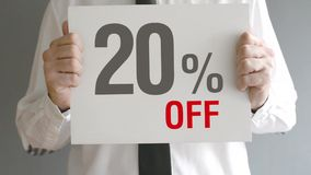 Salesman holding sale tag with twenty percent sales discount price. Consumerism concept. stock footage