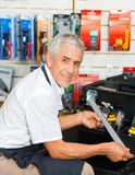 Salesman Holding Tool In Hardware Store Stock Photos