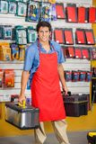 Salesman Holding Toolboxes In Hardware Shop. Portrait of smiling young salesman holding toolboxes in hardware shop Stock Photography