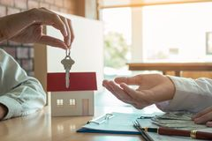 Salesman home brokers provide key to new homeowners. Salesman home brokers provide key to new homeowners Stock Photo