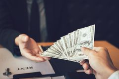 Salesman home brokers receive cash with buyers giving money for salesman.  royalty free stock image