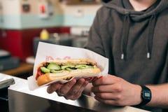 Salesman with hotdog in fast food snack bar. Hotdog - friendly salesman and customer in a fast food snack bar stock photo