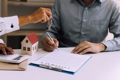 Salesman house brokers provide key to new homeowners in office.  royalty free stock photography