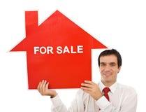 Salesman with house for sale sign. Salesman smiling holding house for sale sign - isolated Stock Images