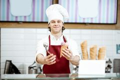 Salesman with ice cream in the shop. Portrait of a handsome salesman in red apron and hat selling ice cream at the modern pastry shop royalty free stock image