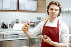 Salesman with ice cream in the shop. Portrait of a young and happy salesman in red apron standing with ice cream cone in the modern pastry shop stock photography
