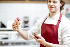 Salesman with ice cream in the shop. Portrait of a young and happy salesman in red apron standing with ice cream cone in the modern pastry shop royalty free stock photos