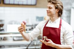 Salesman with ice cream in the shop. Portrait of a young and happy salesman in red apron standing with ice cream cone in the modern pastry shop stock images