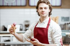 Salesman with ice cream in the shop. Portrait of a young and happy salesman in red apron standing with ice cream cone in the modern pastry shop stock photo