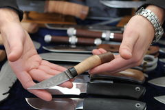 Salesman of knifes. Two hands of a young salesman are showing a nife stock photo