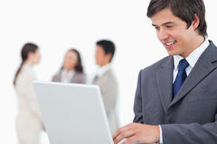 Salesman with laptop and colleagues behind him Royalty Free Stock Photos