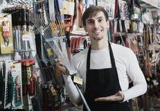Salesman with leaf rake in supermarket Royalty Free Stock Photos
