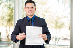 Salesman with a lease. Handsome young salesman inviting you to sign a lease or a service agreement Royalty Free Stock Images