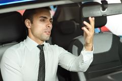 Salesman is looking in rearviev mirrow. He is in classic white shirt, sitting in new car royalty free stock image