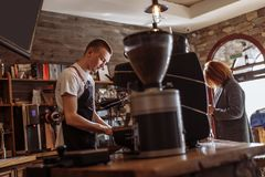Salesman is making coffee for woman stock photography