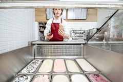 Salesman making ice cream in the pastry shop. Salesman making ice cream in the waffle cone while standing near the ice cream trays at the pastry shop, wide angle royalty free stock photography