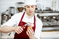 Salesman making ice cream at the pastry shop. Young salesman in apron and hat making ice cream with waffle cone at the modern pastry shop royalty free stock photography