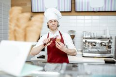 Salesman making ice cream at the pastry shop. Young salesman in apron and hat making ice cream with waffle cone at the modern pastry shop stock images