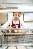 Salesman making ice cream at the pastry shop. Young salesman putting ice cream ball into the waffle cone with professional tool at the pastry shop stock image
