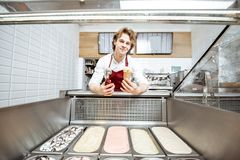 Salesman making ice cream in the pastry shop. Salesman making ice cream in the waffle cone while standing near the ice cream trays at the pastry shop, wide angle stock images