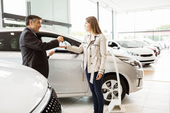 Salesman offering car key to a customers. At new car showroom Stock Image