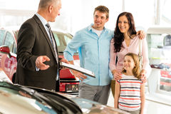 Salesman offering a car to family. Car dealer offering a car to smiling family royalty free stock photography
