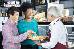 Salesman Offering Cheese Samples To Customers In Shop. Happy salesman offering free cheese samples to customers in shop Royalty Free Stock Image