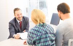 Salesman offering contract. Toned of salesman or manager offering contract to young couple concerning buying apartment, flat, car or automobile. Agreement or royalty free stock image