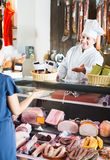 Salesman offering sausages to young woman in delicatessen shop Royalty Free Stock Images